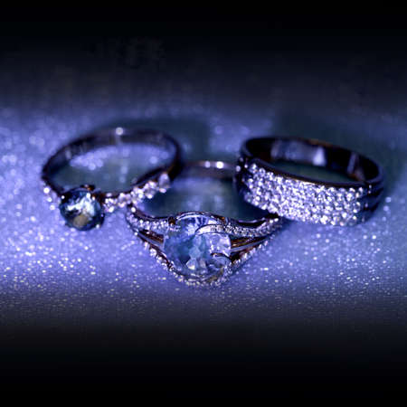 jewelle: Golden jewelry accessories - rings with brilliants on blue dark background