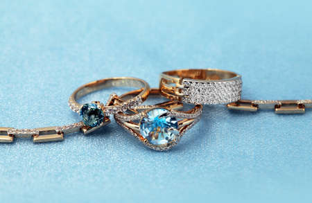 jewelle: Golden jewelry accessories - rings with brilliants on blue background Stock Photo