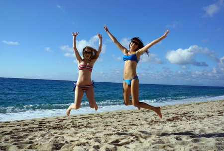 high jump:  Young active women - girl friends high jump on a beach, Italy