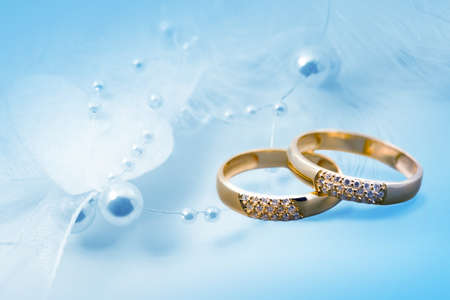 Wedding rings on blue background for card
