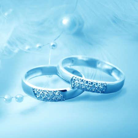 goldy: Anelli di nozze su sfondo blu per la carta Archivio Fotografico