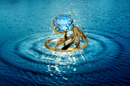 Jewelry golden topaz ring in water waves photo
