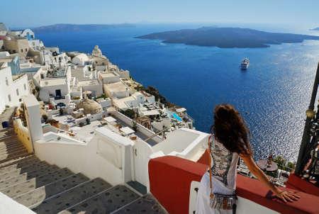 Beautiful woman on holidays, Santorini Thira town view Фото со стока