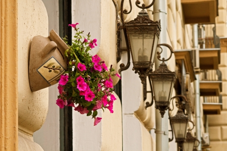 ornamental flowerpot with pink flowers on the building wall Stock Photo