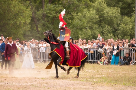 joust: Moscow, Russia - June 23, 2013: Times and Epoch-2013 festival in Kolomenskoye park. The Middle Ages (Srednevekove). Knight on a horse in a historical reconstruction on the joust.