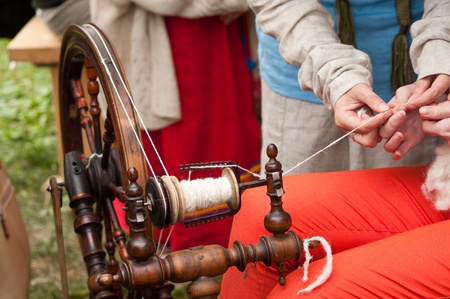 spinning-wheel with hands making yarn from the wool photo