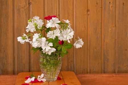 bouquet of white flowers and red roses on the ragged old wooden wall background photo