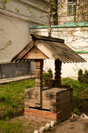 Wooden water well in the street photo