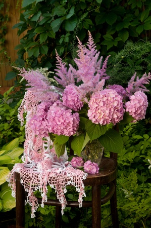 Still life bouquet with pink hydrangea and astilba on the old chair photo