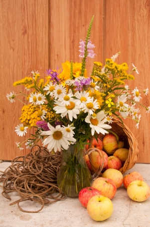 still life of wild flowers and apples photo
