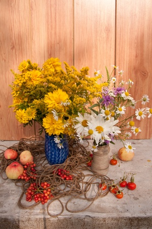 two bouquets of wild flowers and apples photo