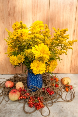 still life bouquet of yellow wild flowers and apples photo