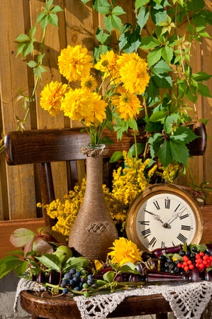 still life with yellow flowers and clock photo