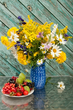 still life bouquet of chamomiles, yellow and blue flowers on the blue vase with berries on the plate photo