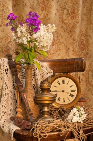 reloj antiguo: Bodegón con phlox ramo en un florero de la vendimia en la vieja silla con reloj antiguo y una lámpara de aceite