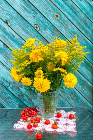 yellow wild flowers bouquet with red berries still life photo