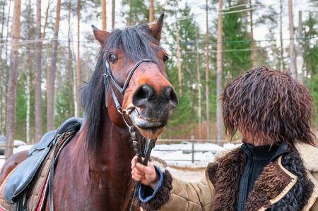 circassian: circassian man in furry hat holding horse