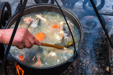 cooking fish soup in a pot on the fireplace photo