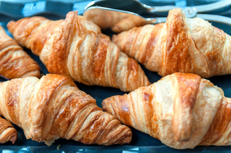 group of croissant laying on the blue tablecloth photo