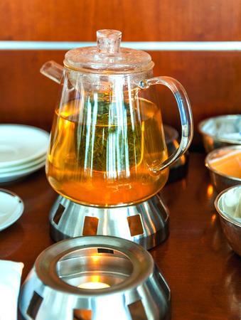 making leaf tea in transparent glass teapot photo