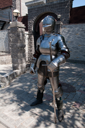 knight in the ancient metal armor standing near the stone wall photo