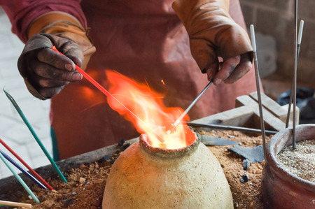 glassblower: Glass artist in his workshop  making glass beads in traditional style  Stock Photo