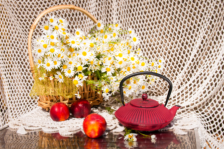 still life of chamomilies bouquet in the basket, peaches and tea pot photo