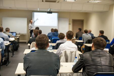 bakifrån av personer som sitter i klassen vid bordet och lyssna presentationen Stockfoto