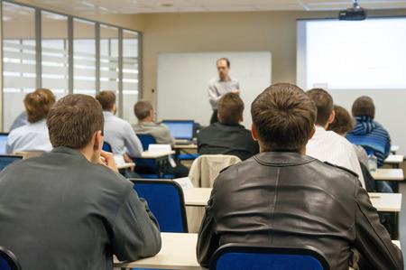 utbildning: presentatör nära skärmen och personer som sitter bak och titta på konferensen