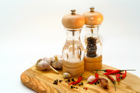 kitchen tool: salt and pepper mill with ingredients around on wooden cutting board isolated on white background Stock Photo