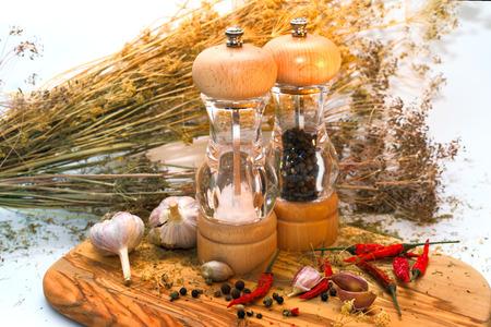 Salz- und Pfeffermühle mit Zutaten um auf hölzernen Schneidebrett