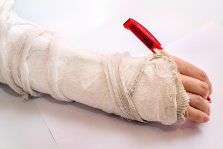 hand writing with the red pen with medicine bandage on injury elbow