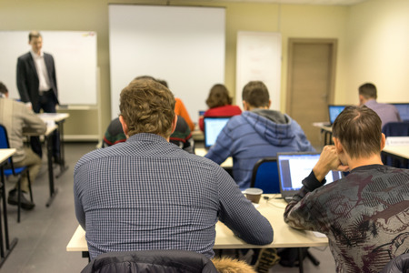 class room: people sitting rear at the computer class at the desks with notebooks and the trainer near the screen explaining the task