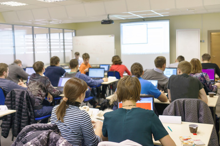 people sitting rear at the computer class at the desks with notebooks and the trainer near the screen explaining the task