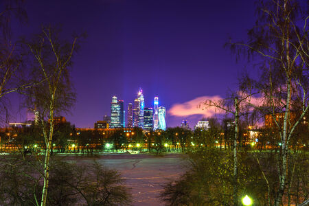 Moscow city skyscrapers by the winter night. View from the river throw birch trees. photo