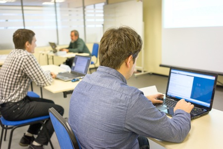 people sitting at the desks and printing on the keyboards of their notebooks in a training class and the coach at the backstage
