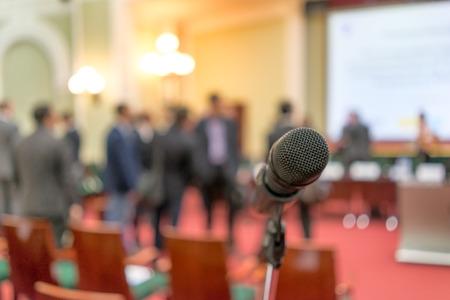Mikrofon fókuszban ellen homályos székek és állva beszélgetett a közönség Stock fotó