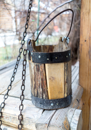Detail of old draw well with wooden bucket on a metal chain close up view in Izmailovo Kremlin, Moscow, Russia photo