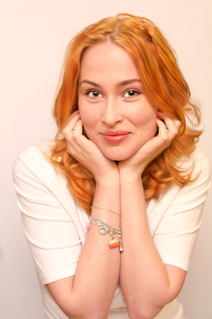 leaning on elbows: portrait of a ginger young woman smiling rests her face on elbows on white background Stock Photo