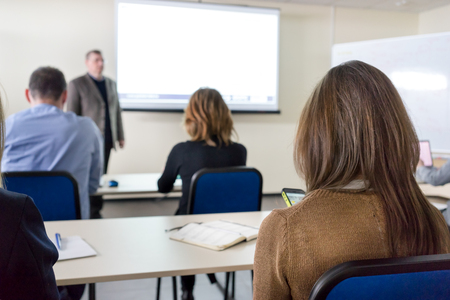 adult learning: people sitting rear at the desks in the education class and the lecturer near the white desk
