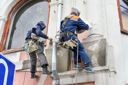 two high workers making repairs on a facade