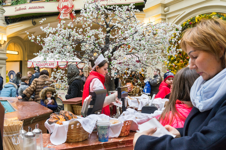 large store: MOSCOW - MARCH 22: A buyer choosing a baking in the GUM store on March 22, 2015 in Moscow. GUM is the large store facing Red Square. It is popular among international tourists.