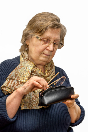 old woman in a glasses putting the second glasses into a spectacle case photo