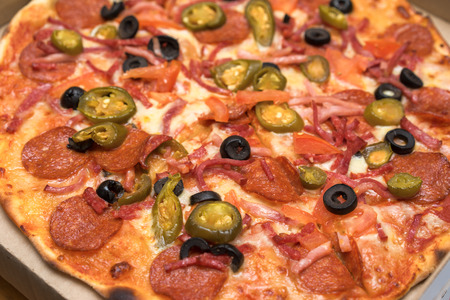unsliced: unsliced pepperoni pizza with olives close up view Stock Photo