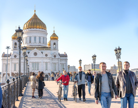tallest bridge: MOSCOW, RUSSIA - APRIL 11, 2015: People walking on the Patriarch bridge against the Cathedral of Christ the Savior. With an overall height of 103 metres, it is the tallest Orthodox church in the world