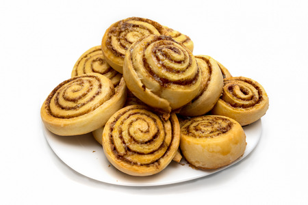 tasty cinnamon rolls on a dish isolated on white