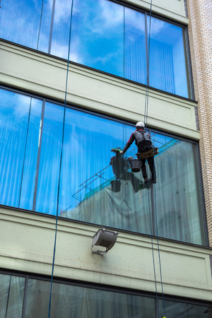 worker cleaning high tower windows photo
