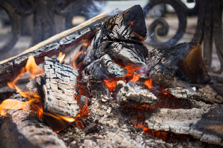 smoldering: Burning smoldering firewood in the fireplace close up. Firewood. Coals. Extinguished the fire. The ashes.