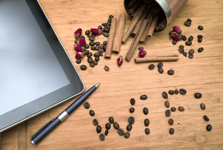 office workers coffee break: composition of tablet, wifi world composed of coffee beans, cup of coffee with milk photo