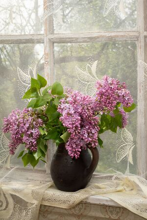 sill: Lush bouquet of lilac in a brown clay vase on a window sill Stock Photo